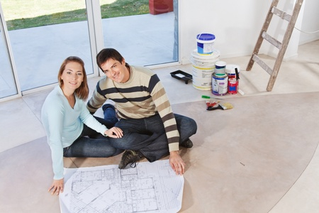 Happy young couple sitting together with blueprint and color buckets in the background photo