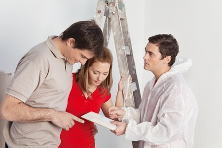 Young couple discussing color options with house painter photo