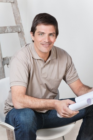 Portrait of young handsome man holding with blueprint photo