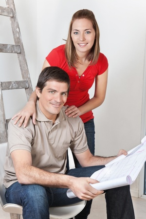 Portrait of young happy couple together with blueprints photo