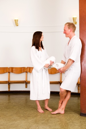 white robe: Man and woman in a wellness spa waiting room, visiting and smiling