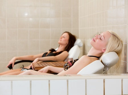 Two women relaxing at poolside in a spa photo