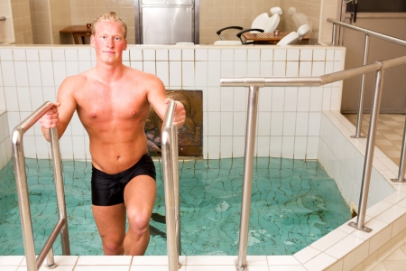 exiting: An attractive caucasian man exiting pool in a spa Stock Photo