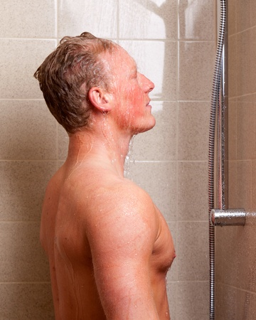 A man standing in a shower with water on face photo