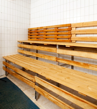 Detail of a sauna interior with tile walls and wooden benches photo
