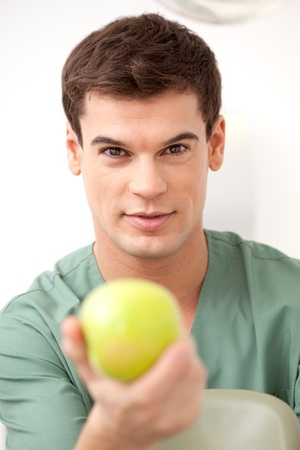 checkup: Happy young man dentist holding an apple out to the camera
