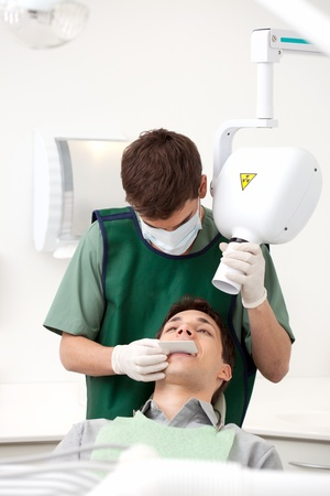 radiology: Dentist preparing x-ray machine on young male patient