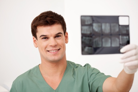 male dentist: A smiling happy dentist holding x-rays, looking at the camera Stock Photo
