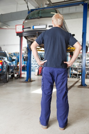Rear view of mechanic looking at car in auto repair shop with hands on waist photo