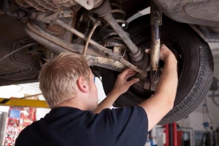 cv: Un meccanico di sesso maschile di ispezione di una comune CV su una vettura in un negozio di riparazioni auto Archivio Fotografico