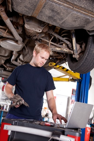 A mechanic in a garage looking at a laptop photo