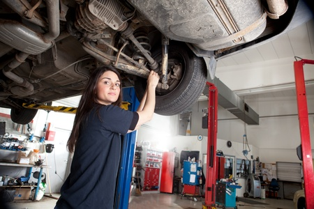 Portrait of a woman mechanic working on the underside of a car photo