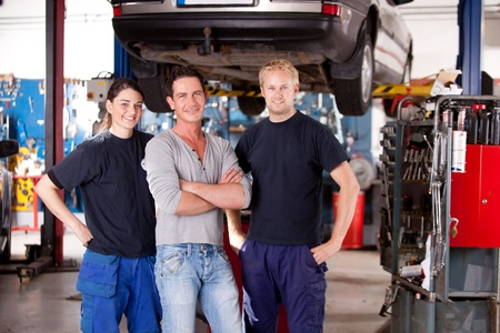 A team of mechanics in a shop with a car on a hoist photo