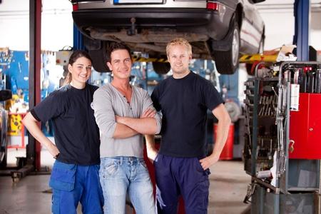 hijsen: Een team van monteurs in een winkel met een auto op een takel