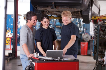 Team of mechanics looking at a laptop in a auto repair shop photo