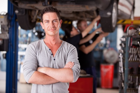 Portrait of a male mechanic looking at the camera with workers in the background photo