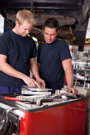A pair of mechanics working on a car looking a service order photo