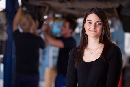 Een gelukkig vrouwelijke auto repareren klant op zoek naar de camera met een glimlach