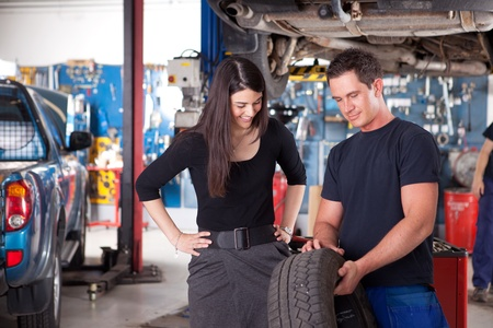 auto service: A mechanic showing the tread of a tire to a female customer