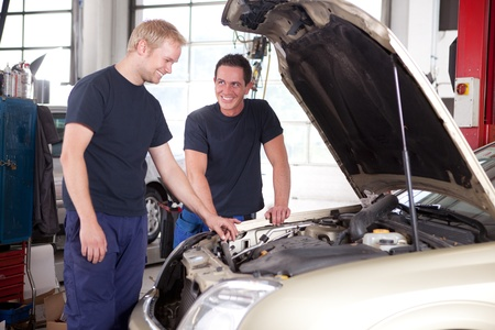 Two mechanics looking at and working on a car in a repair shop Stock Photo - 10177933
