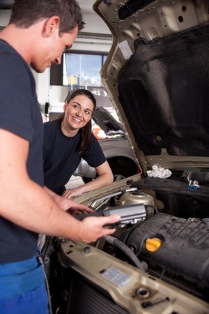 motor mechanic: A man and a woman mechanic team doing service on a car in a garage Stock Photo