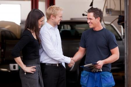 honestidad: Un mec�nico atractivo feliz estrecharme la mano con un par de clientes, feliz con su servicio Foto de archivo