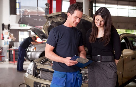 servicing: A man mechanic and woman customer discussing repairs done to her vehicle Stock Photo