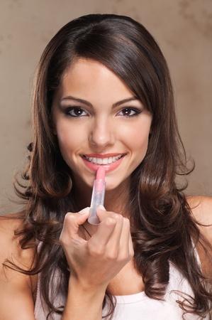 mujer maquillandose: Close-up retrato de mujer aplicar el lápiz labial y sonriente