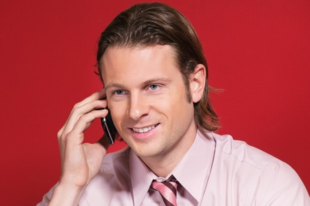 telecommunicating: Happy businessman talking on a mobile phone against colored background