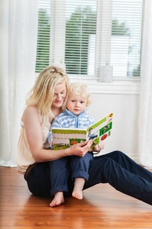 乳幼児: 母親と赤ちゃんが床に座って本を読んで 写真素材