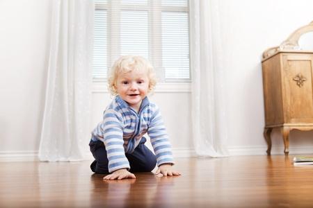 Portrait of happy cute child crawling on floor photo