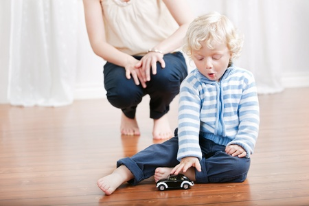 Expressive baby boy playing with a toy car with mother in the background photo