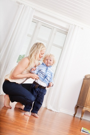 scandinavian people: Full length of young mother and cute little child at home