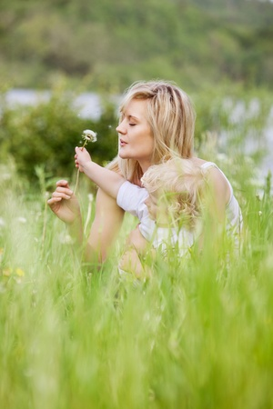 Mother and son making wishes blowing the seeds off a dandelion photo