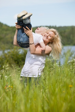 Blond woman standing in meadow playing with toddler son Stock Photo - 10336923