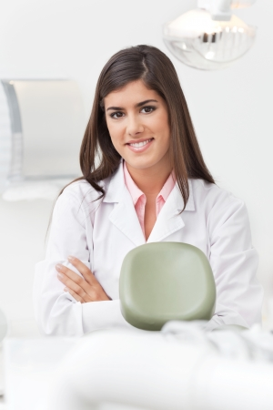 Portrait of beautiful young female dentist at her office smiling photo