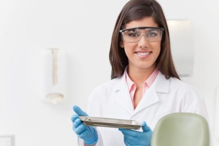 dental hygienist: Smiling beautiful dentist holding tray of dental instruments Stock Photo