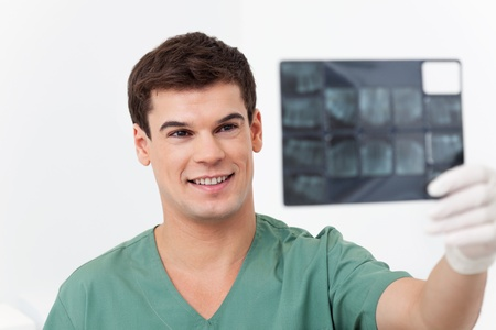 Young smiling doctor analyzing a dental X-Ray detail photo