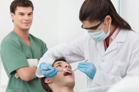 Close-up of medical dentist procedure of teeth cleaning photo