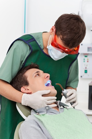Young man going through therapy of tooth in clinic photo