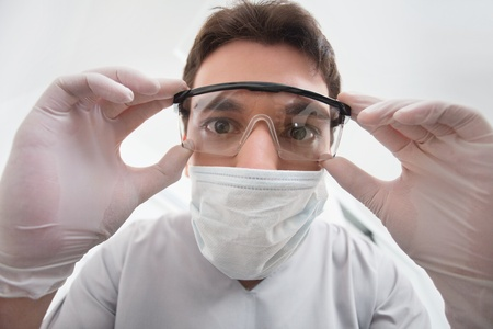 hygienist: Close-up of young dentist adjusting his eyewear