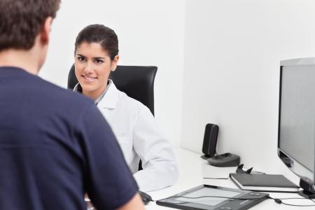 comunicacion oral: Sonriente joven m�dico hablando al paciente en su Oficina