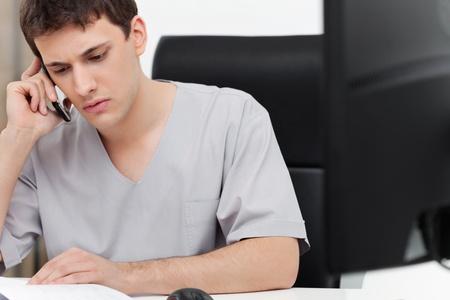 comunicacion oral: Dentista joven grave tener conversación en el teléfono móvil