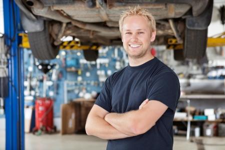 Portret van vrolijke jonge monteur met gekruiste armen staan in zijn auto reparatiewerkplaats Stockfoto