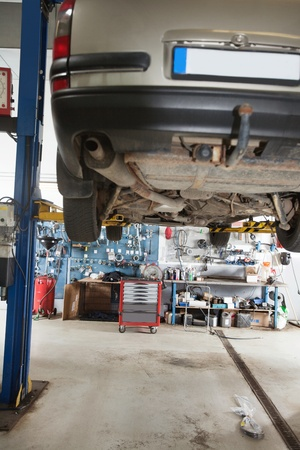 car garage: Car under repair on service lift in garage Stock Photo