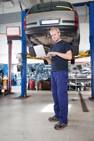 mecanico automotriz: Retrato de longitud completa de la sonriente joven mecánico mediante ordenador portátil en su taller de reparación automática Foto de archivo