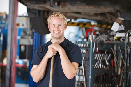 Portrait of smiling young mechanic leaning on a broom in a garage photo