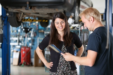 two car garage: Young mechanic and woman looking at notepad and smiling in garage Stock Photo