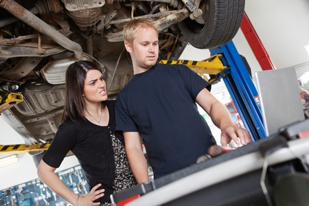 Irritated young woman standing with mechanic using laptop in garage photo