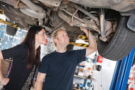 Young mechanic and woman looking at machine of car in auto repair shop photo